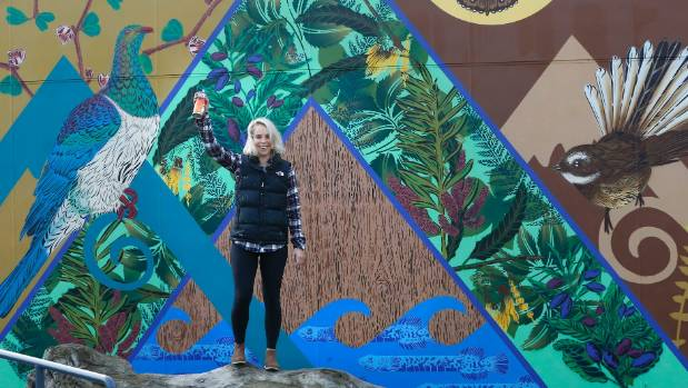 Auckland artist Flox with a mural she painted at St Andrew's school near Timaru. When working outside her home city, she tailors her art to local themes.